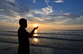 Silhouette of muslim pray near the beach when sun rising up Stock Photo