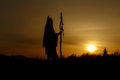 silhouette of native american shaman with pikestaff on background of sunset beutiful in mountains Royalty Free Stock Photo