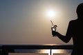 Silhouette of nude girl with cocktail in hands on sunset background Royalty Free Stock Photo