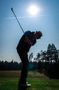 Silhouette of old man playing golf senior citizen is wearing a hat and swinging the club with sun and airplane contrails in the Stock Photos