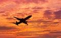 Silhouette passenger airplane flying on sunset
