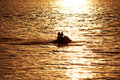 Silhouette of people on jet ski against the sunset at sea Stock Image