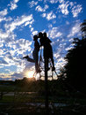 Silhouette Photo of Man and Woman Kissing Under White and Blue Sky during Sunset