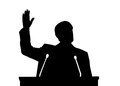 Silhouette of politician who talks on stage with hand high in the air Royalty Free Stock Photos
