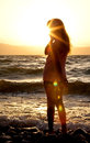 Silhouette of a pretty girl at the beach at sunset in summer evening Royalty Free Stock Photo