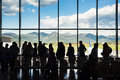 Silhouette queue people waiting in line for airplane in terminal with mountain background Royalty Free Stock Photo