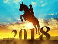 Silhouette the rider on the horse jumping into the New Year 2018. Royalty Free Stock Photo
