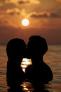 Silhouette of romantic couple standing in sea kissing Stock Image
