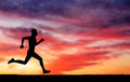 Silhouette of running man against the colorful sky on sunset fiery background Royalty Free Stock Image
