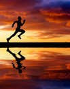 Silhouette of running man on sunset fiery background. Royalty Free Stock Photo