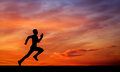 Silhouette of running man on sunset fiery sky background Royalty Free Stock Photo