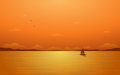 Silhouette sailboat in flat icon design and sunset sky background Royalty Free Stock Photo