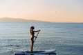 Silhouette of girl with sup surf and paddle in hands at the ocean. Concept lifestyle, sport Royalty Free Stock Photo
