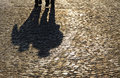 Silhouette shadows people walking brick pavement Royalty Free Stock Image