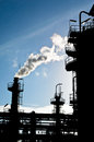 Silhouette of smokestack in petrochemical plant Royalty Free Stock Image