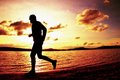 Silhouette of sport active man running and exercising on beach at vivid colorful sunset. Royalty Free Stock Photo