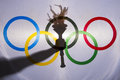 Silhouette of Sport Torch Behind Olympic Flag Royalty Free Stock Photo