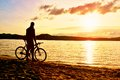 Silhouette of sportsman  holding bicycle on lake bech, colorful  sunset cloudy sky and reflection in wavy water level Royalty Free Stock Photo