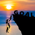Silhouette teamwork of people climbs into cliff to reach the word GOAL sunrise (goal setting business concept)