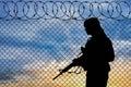Silhouette terrorist near the border concept of terrorism fence at sunset Stock Photos