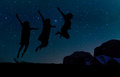 Silhouette of three people jumping on the sand hill, beneath the stars, Milky Way and stars over the mountain at Wadi Rum Royalty Free Stock Photo