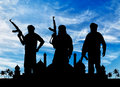 Silhouette of three terrorists concept terrorism with a weapon against a background sunrise and the town hall with palm Stock Image
