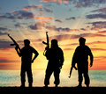 Silhouette of three terrorists concept terrorism with a weapon against a background sunset Stock Images
