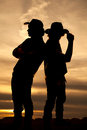 Silhouette of two cowboys standing back to back in the sunset Royalty Free Stock Photo