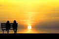 Silhouette of two friends sitting on wood bench near beach staring at flying bird Stock Photo