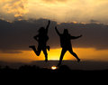 Silhouette of two girls jumping with beautiful sunset Royalty Free Stock Photo