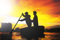 Silhouette of two men rowing in woven bamboo basket boat Royalty Free Stock Photo