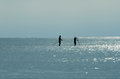 Silhouette of two paddle boarders out in the ocean waters during the early morning rising sun Royalty Free Stock Photo