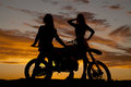 Silhouette two women stand by motorcycle a of standing a Royalty Free Stock Photo