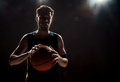 Silhouette view of a basketball player holding basket ball on black background Royalty Free Stock Photo