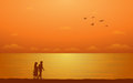 Silhouette walking couple on beach in flat icon design under sunset sky background Royalty Free Stock Photo