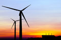 Silhouette wind turbine generator with factory emissions of carb carbon credits concept carbon dioxide on sunset background Royalty Free Stock Images