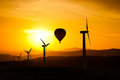 Silhouette of wind turbines and a hot air balloon f mountains and the sunset Royalty Free Stock Photo