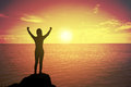 Silhouette of winning success woman at sunset or sunrise standing and raising up hand in celebration of having reached mountain. Royalty Free Stock Photo