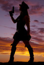 Silhouette of a woman cop gun up female holding her Royalty Free Stock Photography