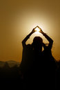 Silhouette of woman hands holding sun in triangle on background Royalty Free Stock Photo