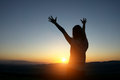 Silhouette woman Hands up against sunset Royalty Free Stock Photo