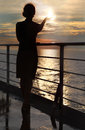 Silhouette of woman holding sun, standing on deck Royalty Free Stock Photo