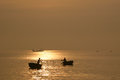 Silhouette of woman and man rowing in woven bamboo basket boat sunrise phuoc hai fishing wharf vung tau province vietnam Stock Photos