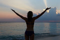 Silhouette of woman with outstretched arms on beach at sunset Stock Image