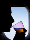 Silhouette of a woman passenger beside airplane window sitting next to the in the drinking beverage Royalty Free Stock Photo