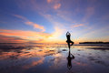 Silhouette woman practicing yoga on the beach at sunset Royalty Free Stock Photo