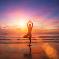 Silhouette of a  woman practicing yoga in the rays of the surrealist sunset at the seaside. Royalty Free Stock Photo