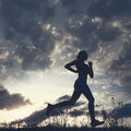 Silhouette woman run under blue sky with clouds Royalty Free Stock Photo
