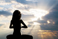 A silhouette of a woman sitting in yoga position Royalty Free Stock Photography