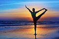 Silhouette of woman stretching at yoga retreat on sunset beach Royalty Free Stock Photo